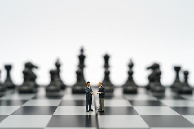 미니어처 사업가 2 명 체스 조각으로 체스 판에 서