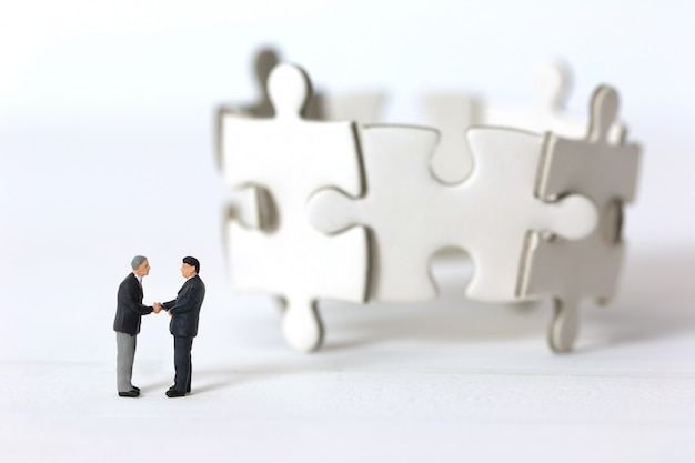 Miniature businessmen shaking hands on blurred group of jigsaw puzzle background.