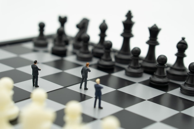 Miniature businessmen standing on a chessboard with a chess piece on the back.