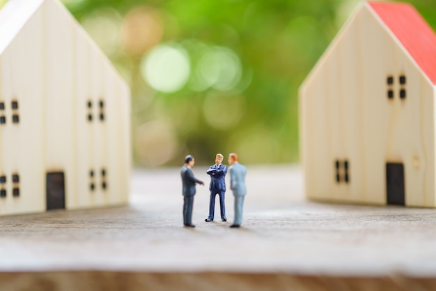 Miniature businessmen standing investment analysis housing or investment in movable property.