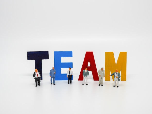 Miniature bussinessman with team word letters on white background