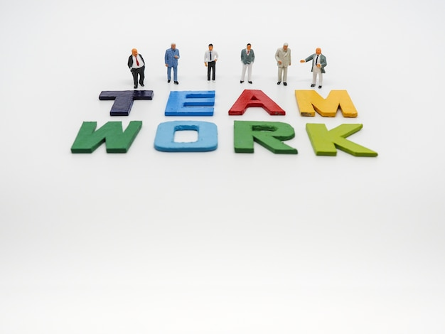 Miniature bussinessman with teamwork word letters on white background