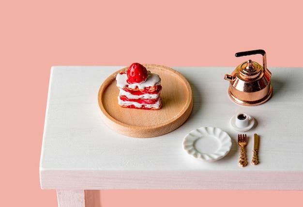 분홍색 배경의 테이블에 있는 미니어처 케이크와 커피 컵