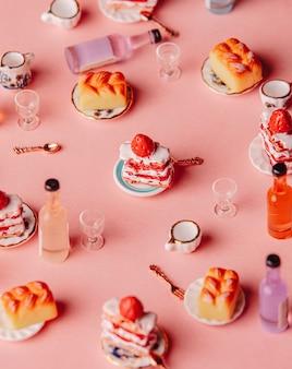 분홍색 배경에 미니어처 케이크와 음료