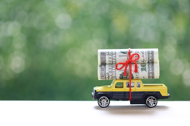 Miniature car and banknotes on nature green background, saving money for car, finance and car loan, investment and business concept