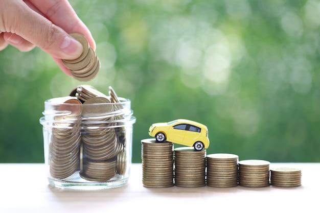 자연 녹색 배경에 동전 더미가 쌓이는 미니어처 자동차 모델, 자동차를 위한 돈 절약, 금융 및 자동차 대출, 투자 및 비즈니스 개념