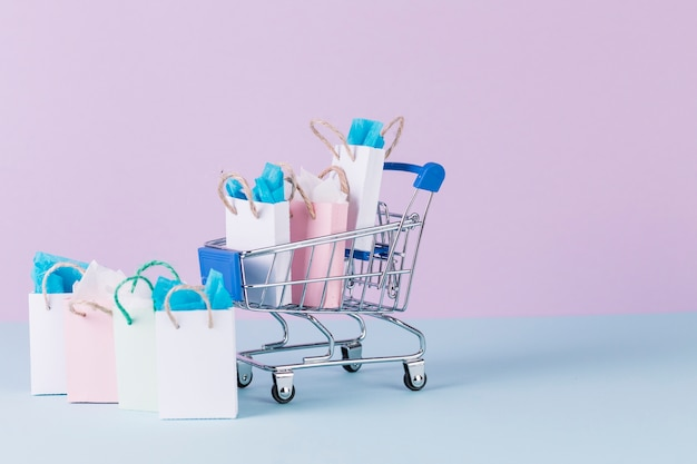 Miniature cart filled with paper shopping bags on blue surface