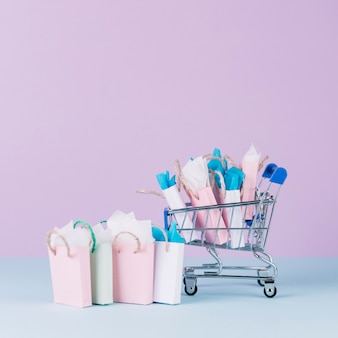 Miniature cart filled with paper shopping bags in front of pink background