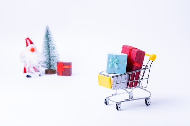 흰색 표면에 선물 미니어처 카트입니다. 크리스마스와 새 해 쇼핑 개념입니다. 확대.
