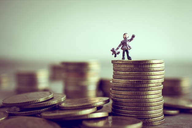Miniature child standing on top of the money save money concept.