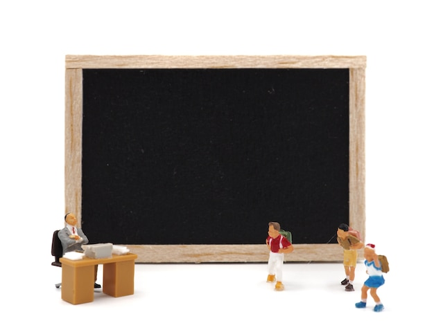 Miniature children standing in front of a blackboard on white background. back to school concept.