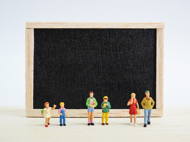 Miniature children standing in front of a blackboard on wooden background. back to school concept.