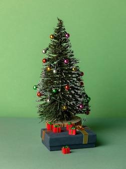 미니어처 크리스마스 트리와 녹색 배경에 선물
