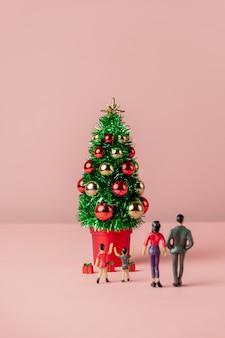 분홍색 배경에 가족과 함께하는 미니어처 크리스마스 트리 및 선물