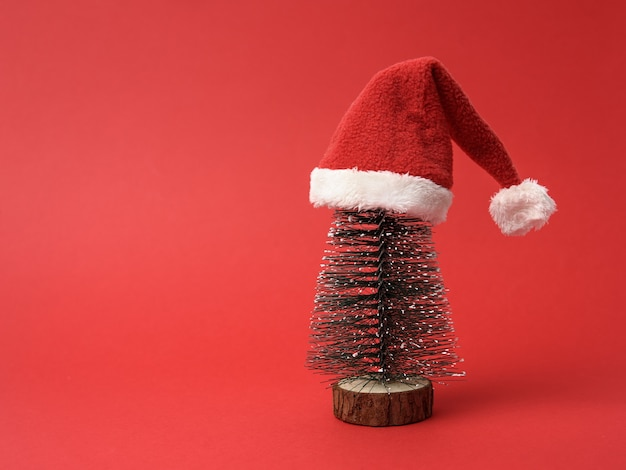 Miniature christmas tree in santa claus hat on a red background, copy space