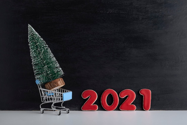 Miniature christmas tree in trolley cart against the background of inscription 2021. purchase and rent of christmas trees.