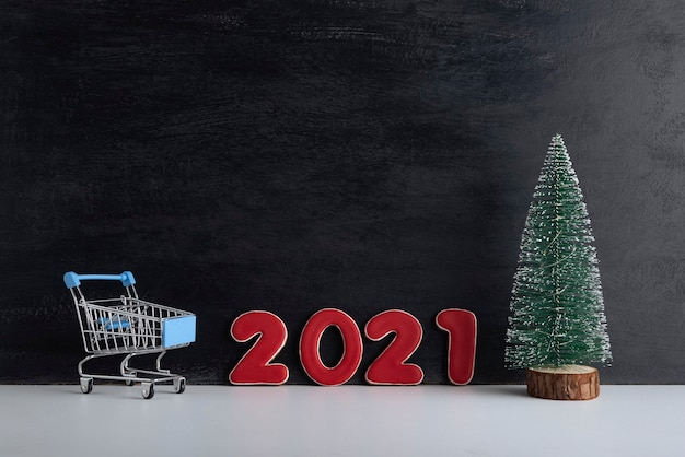 Miniature christmas tree, trolley cart and inscription 2021 on black background. new year shopping.
