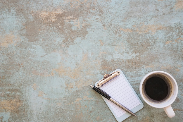 Miniature clipboard with pen and coffee cup on rustic background