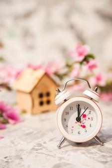 Миниатюрные часы и небольшой деревянный дом крупным планом и копией пространства.