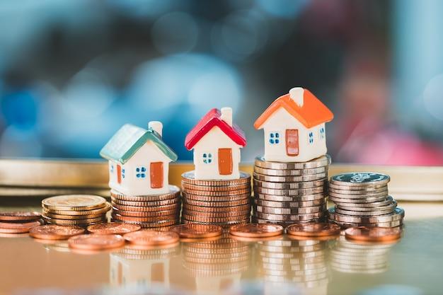 Миниатюрный красочный дом на стопке монет, использующий в качестве недвижимости недвижимость и финансовую концепцию