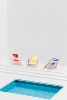 Miniature composition of sunbeds next to swimming pool