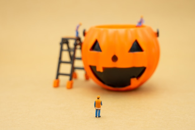 Miniature of construction worker with halloween basket