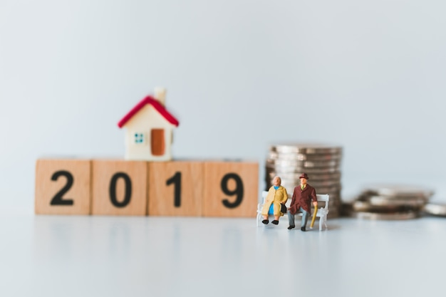 Miniature couple elderly people sitting on wooden year 2019 and stack coins