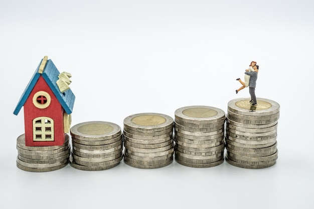 Miniature couple in love on stack of coin with house model