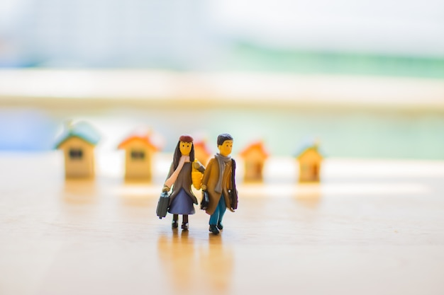 Miniature of couple love with home on wooden table. subject is blurred.