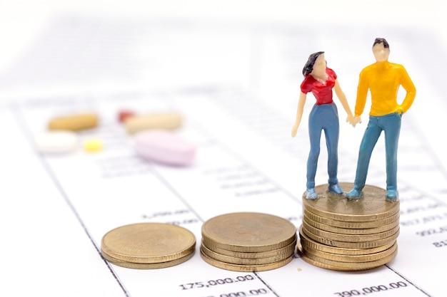 Миниатюрные пары людей и складывают монеты на утверждение и наркотик позади. экономия концепции.