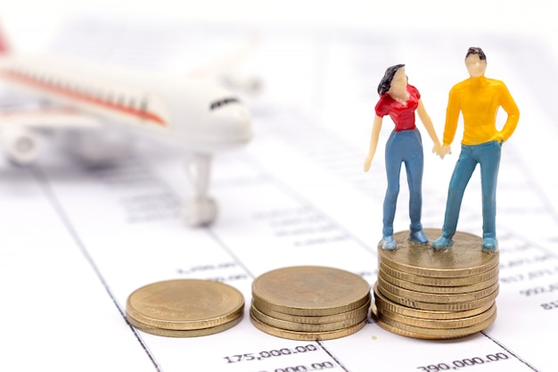 Miniature couple people and stack coins on statement and the airplane behind.