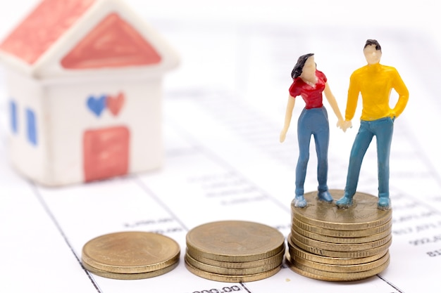 Miniature couple people and stack coins on statement and the house behind. saving and loan concept.