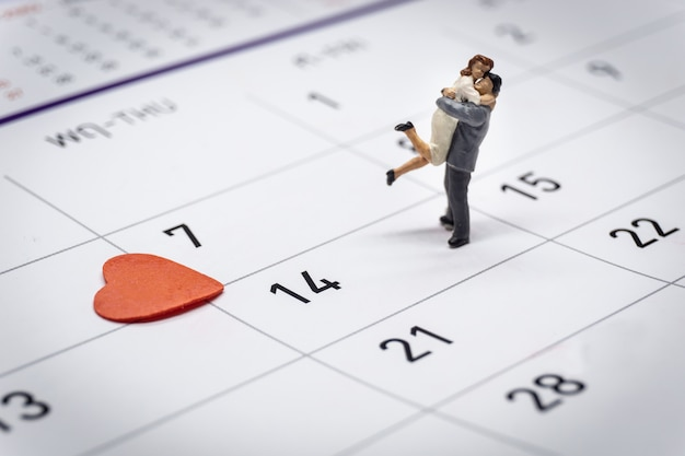 Miniature couple standing on calendar