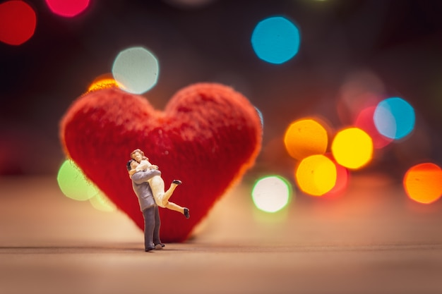 Miniature couple standing on red heart