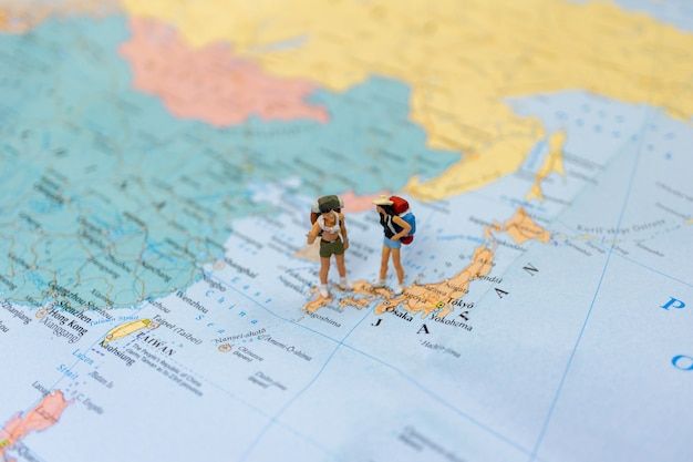 Miniature couple tourist stand and walk on map of  japan in world map.