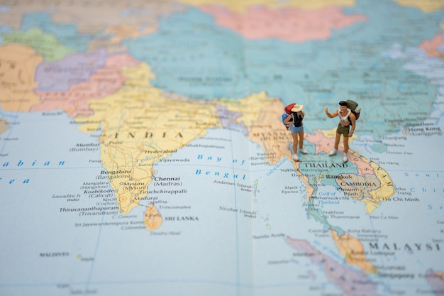 Miniature couple tourist stand and walk on map of thailand in world map.