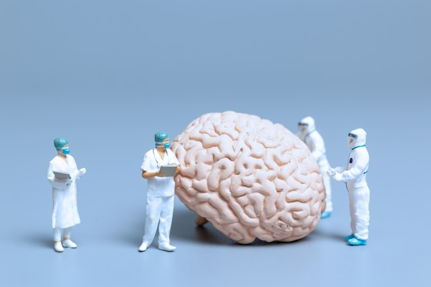 Miniature doctor checking and analysis alzheimer's disease and dementia of brain, science and medicine concept