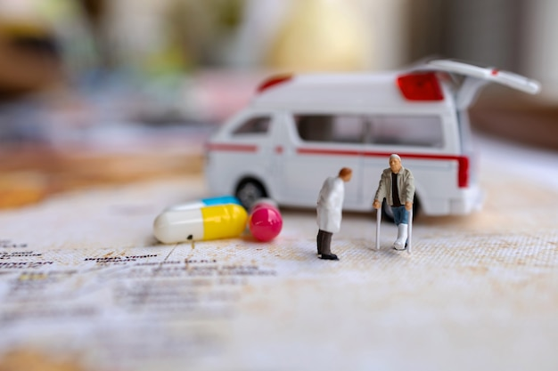 Miniature doctor and patient standing with capsule and ambulance. healthcare concepts.