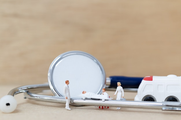 Miniature doctor with nurse carry the patient on a stretcher