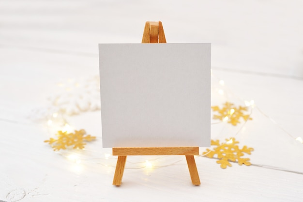 Miniature easel with blank card, pine branches and christmas decorations