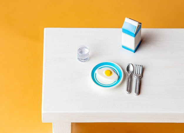 Miniature eggs with milk pack, fork and spoon on wooden table.