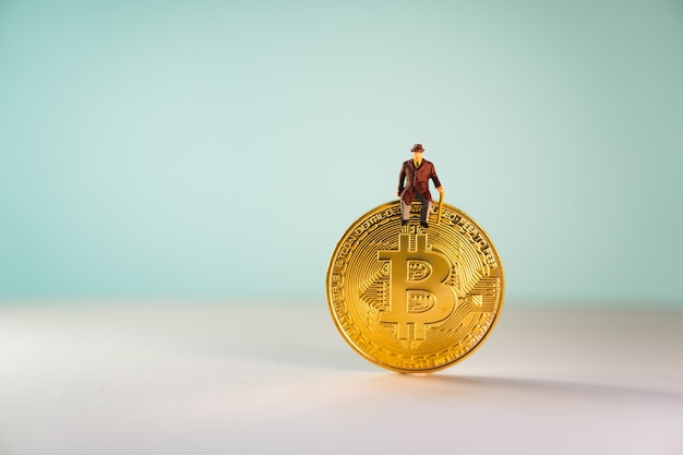 Miniature elderly people sitting on golden coin with bitcoin symbol