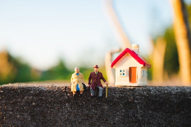 Miniature elderly people sitting with mini house