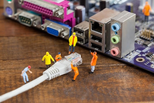 ミニチュアエンジニアと労働者は、プラグインのコンピュータにlanケーブル