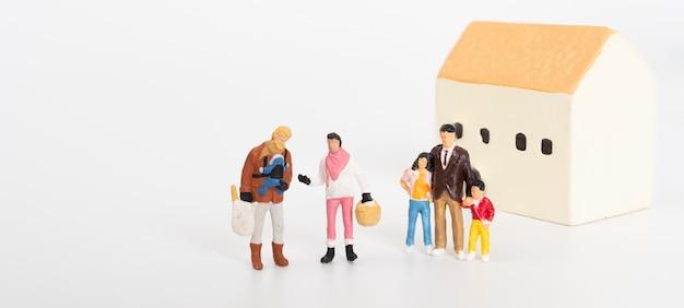 白い背景の上の新しい家に満足してミニチュア家族の人々