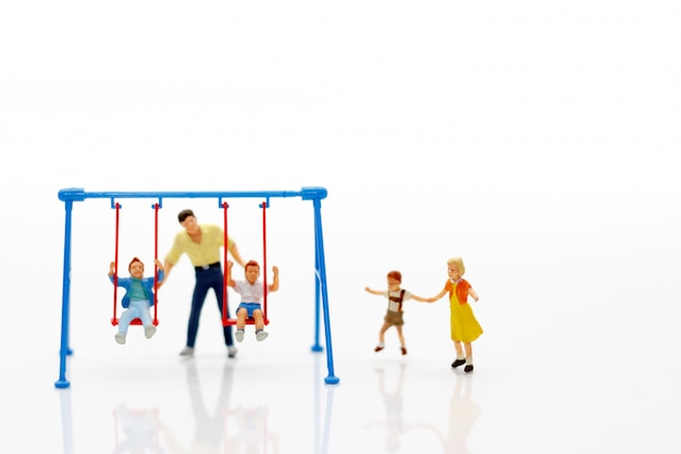Miniature family playing on the swing