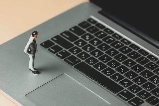 Miniature figure of a businessman on laptop computer