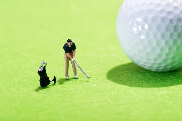 Miniature figure of a golfer playing a stroke