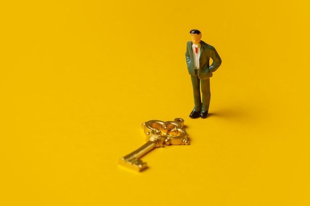 Miniature figure of a man neat golden key on yellow background