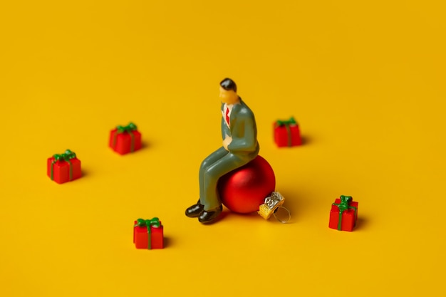 Miniature figure of man sits on christmas bauble surrounded by gifts on yellow surface